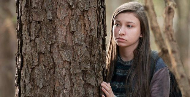 Enid hides behind a tree in a scene from Season 6 of 'The Walking Dead'