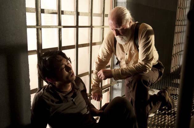 Hershel (Scott Wilson) treats a sick Glenn (Steven Yeun) in a scene from Season 4 of 'The Walking Dead'