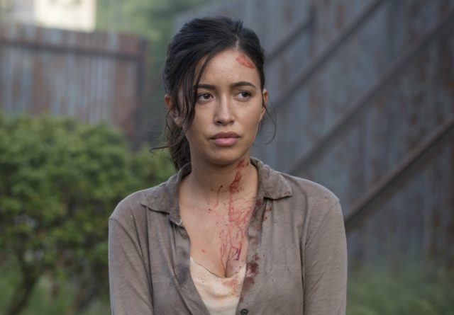 Rosita covered in blood sitting outside.