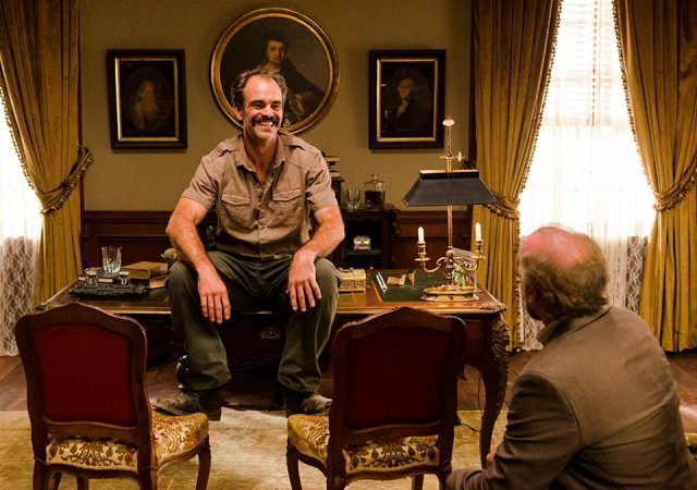 Simon sits on Gregory's desk in a scene from 'The Walking Dead'
