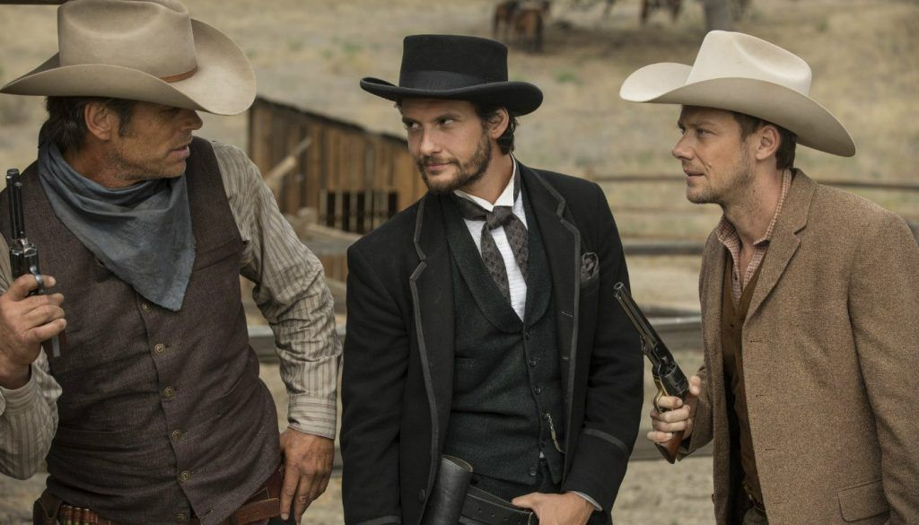 Teddy, Logan, and William stand together and hold guns in a scene from Westworld