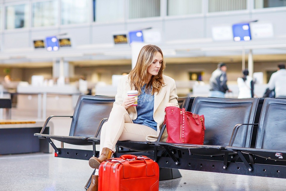 Business woman at international airport sitting and drinking coffee