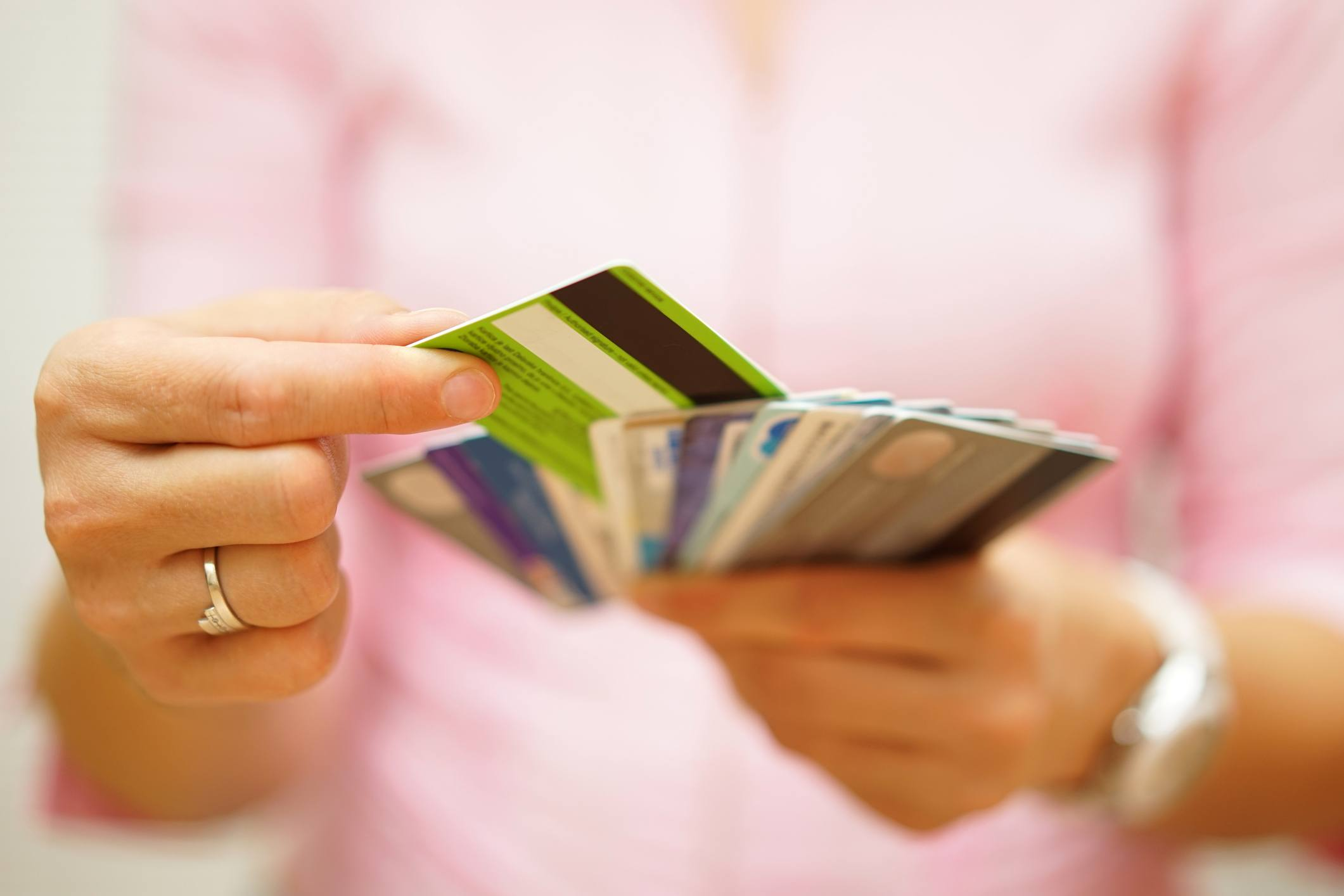 A woman chooses from many credit cards to add to her debt