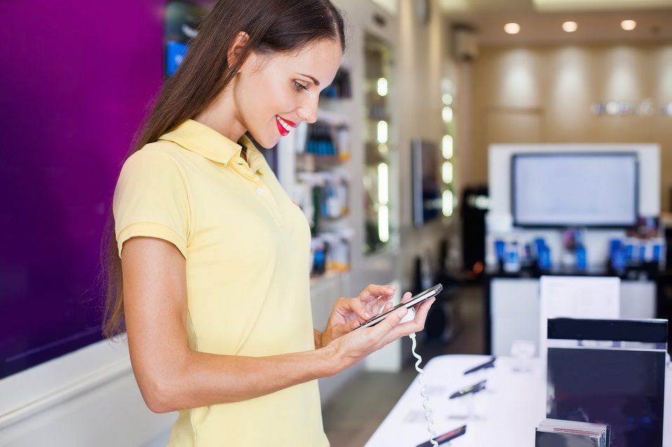 girl standing in a shop and choosing a new mobile phone