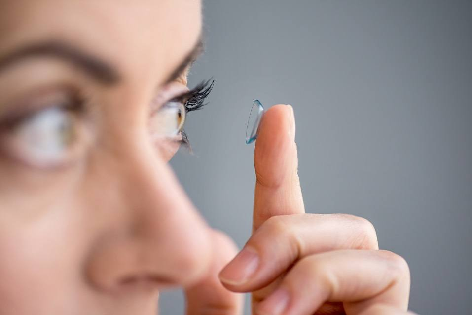 Attractive mature lady putting on contact lenses