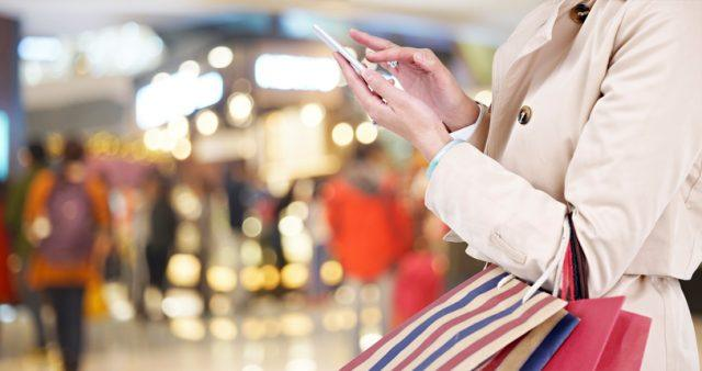 A young woman uses her mobile phone in a store