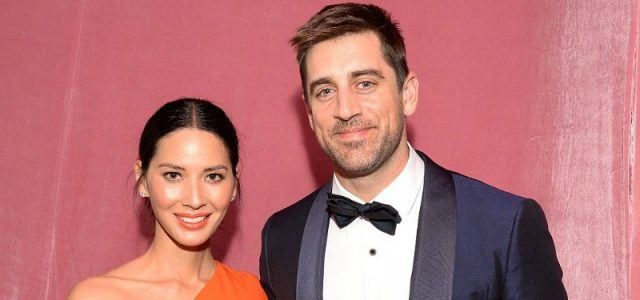 Olivia Munn and Aaron Rodgers stand together in front of a pink wall.