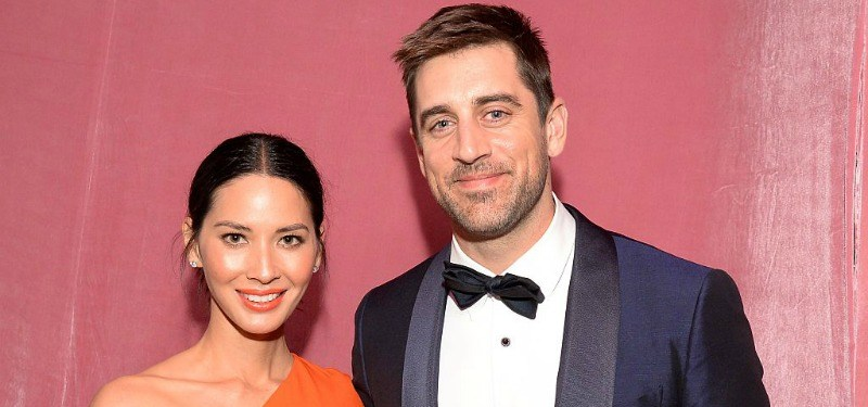 Olivia Munn and Aaron Rodgers smile for cameras at an event