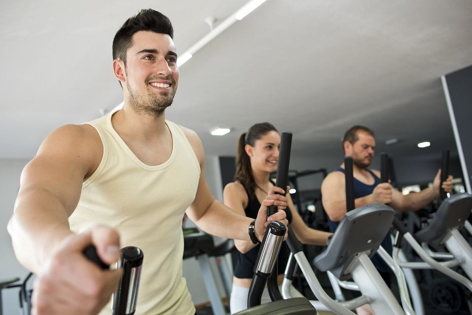 people at gym on elliptical bikes