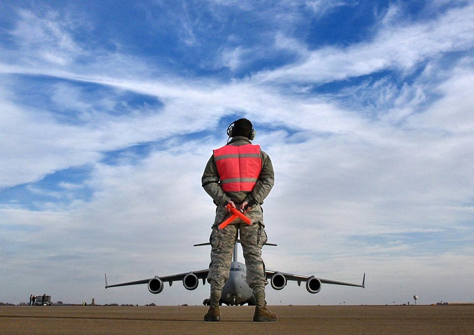 An airman directs a C-130.