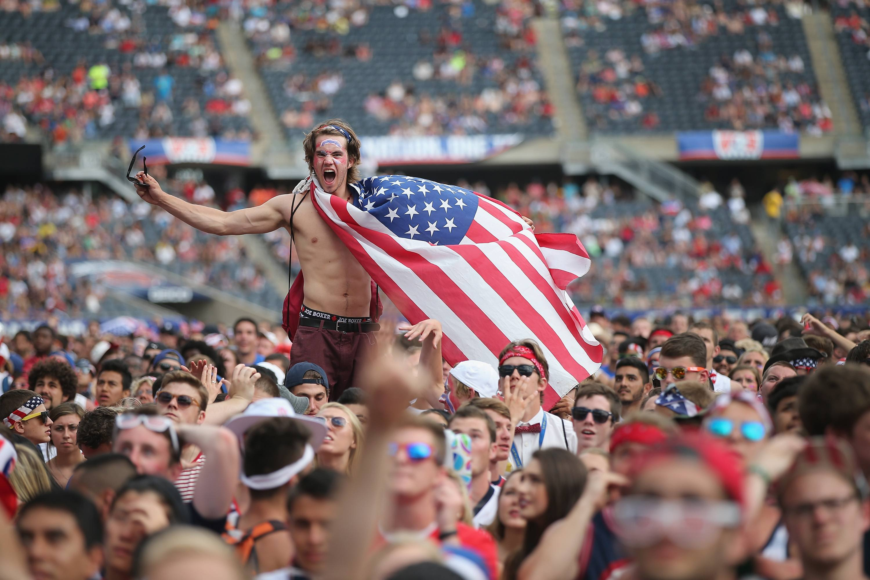 An American soccer fan, draped in a flag
