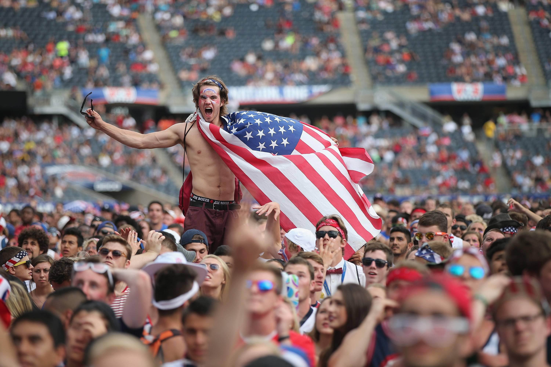 An American soccer fan, draped in a flag