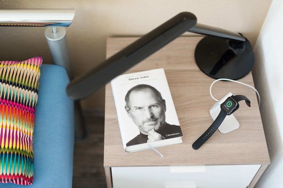 An Apple Watch is being loaded on the bedside table