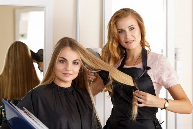 Beautiful blonde female hairdresser holding scissors, comb and hairdryer