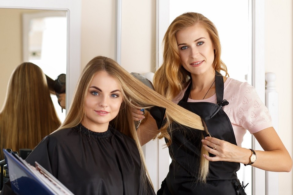 Female hairdresser holding scissors, comb and hairdryer