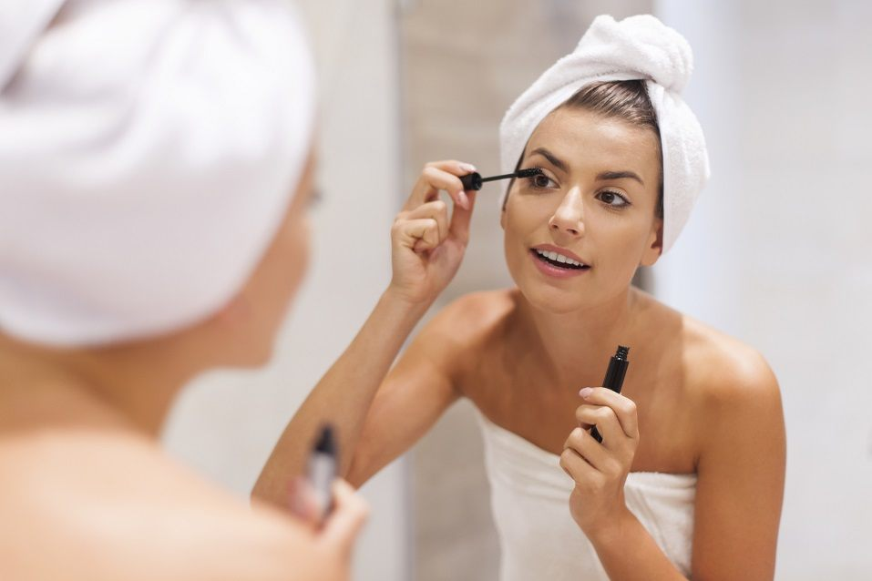 woman using mascara in bathroom