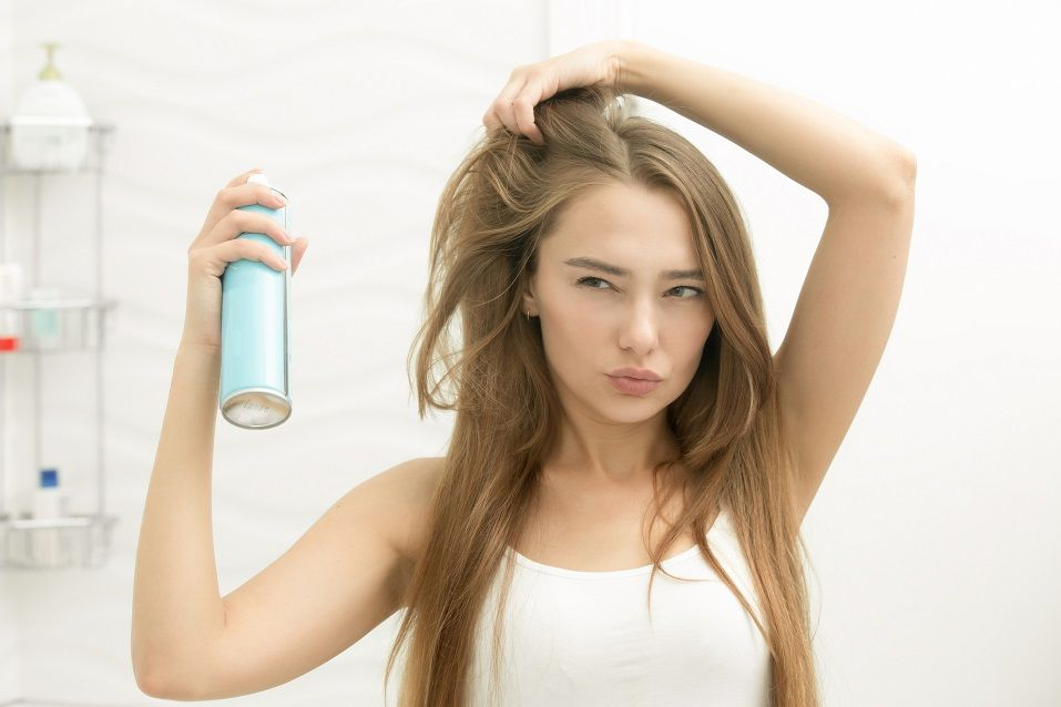 young girl applying hair spray on her hair