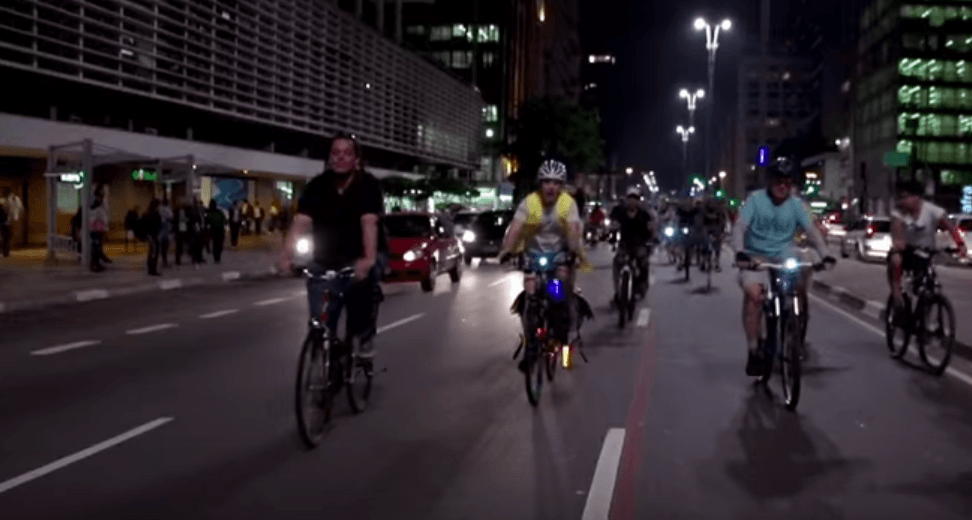 Many people in bikes riding down a street at night alongside cars in Bikes vs. Cars