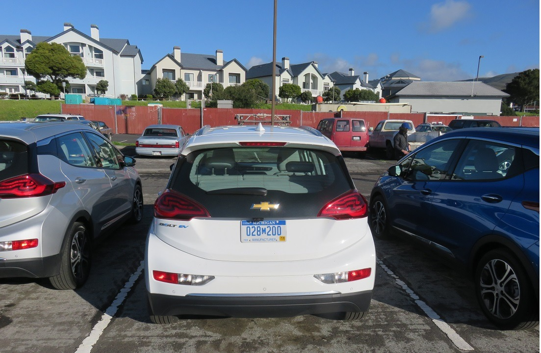 A white 2017 Chevrolet Bolt EV sits parked in a lot across from a residential area