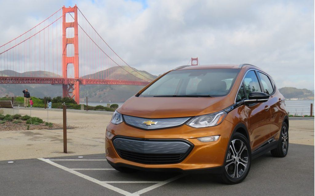 An orange 2017 Chevrolet Bolt EV sits parked in a parking lot overlooking the Golden Gate Bridge in San Francisco, California