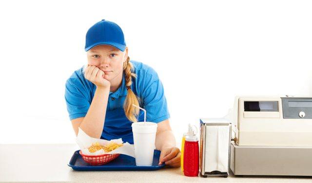 Teenage worker in a fast food restaurant bored and leaning on the counter