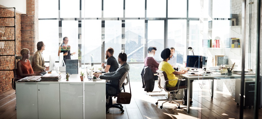 A business team made up of people from around the world is solving tough problems in an open office space