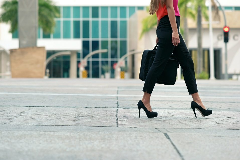 woman walking and carrying a briefcase