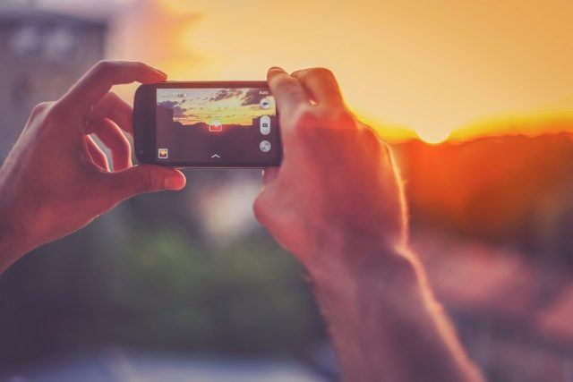 A man captures a sunset with his smartphone