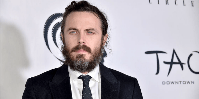 Casey Affleck standing on a red carpet in a black suit and tie