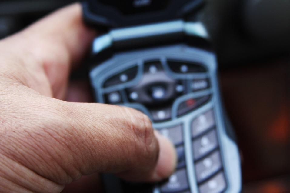 Male dialing a number on a celluar device