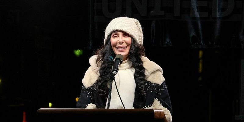 Cher is smiling at a podium wearing a sweater and beanie.