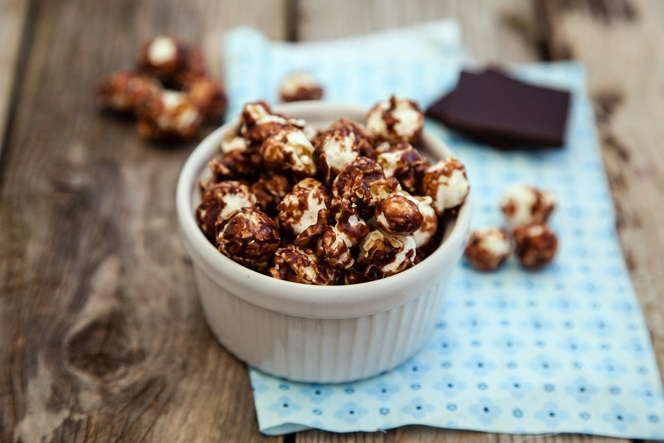 Chocolate covered popcorn in a white bowl