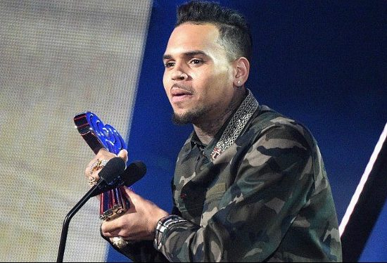 Chris Brown speaking into a microphone, wearing a black leather jacket