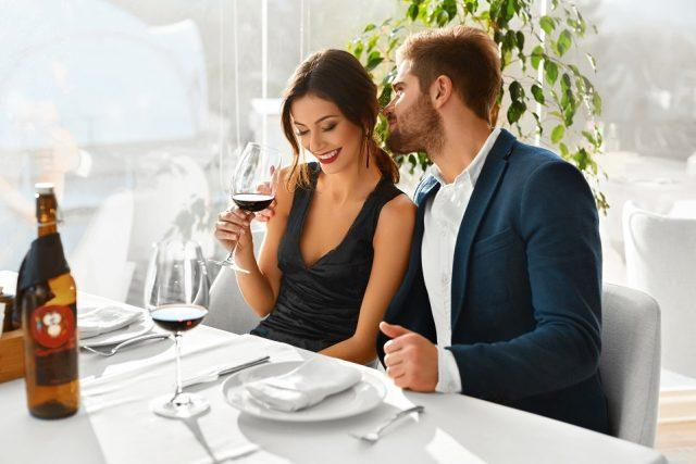 A couple has a romantic dinner at a fancy resturant.