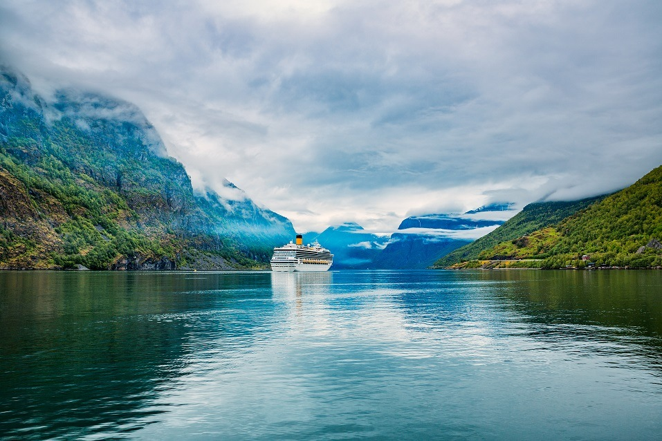 A cruise liner makes its way down a picturesque pathway in Hardangerfjord, Norway