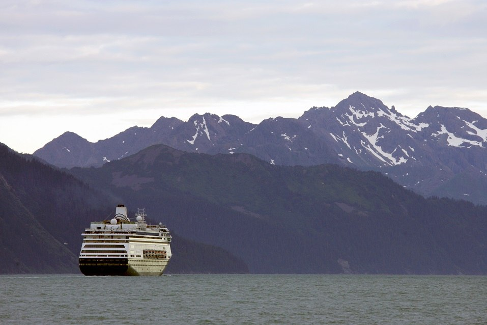 A cruise ship slowly makes its way across Alaska