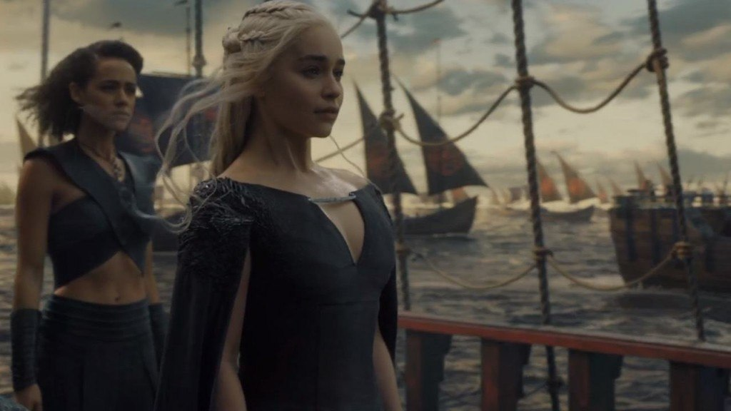 Daenerys, standing on a ship at sea with a fleet at her side