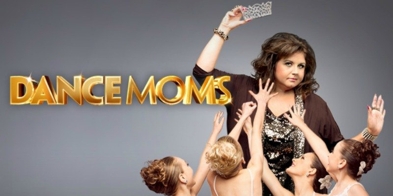 Abby Lee Miller holds a ticket in the air as little girls try to reach for it on Dance Moms.