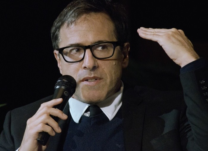 David O. Russell with his left hand flat and held up, speaking into a microphone