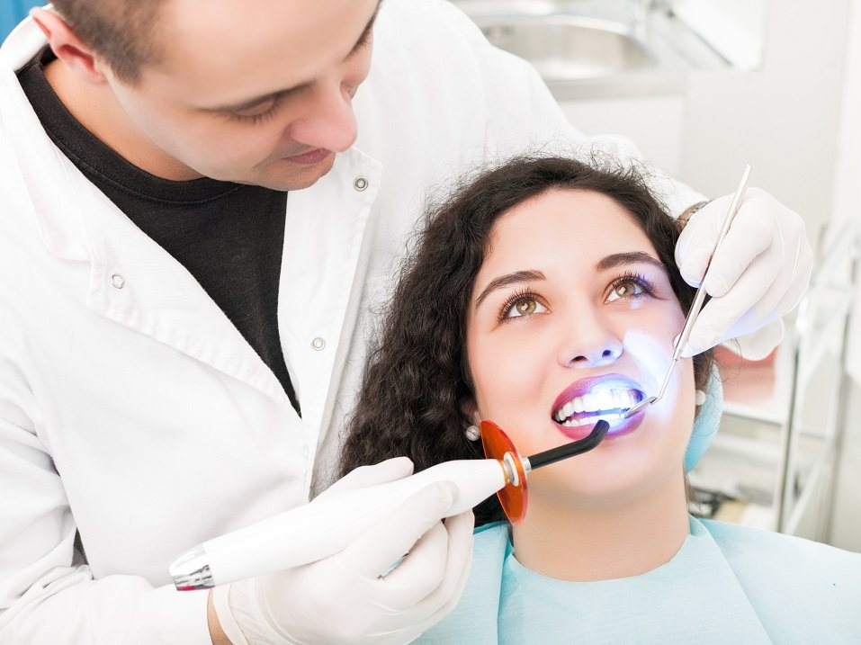 Dentist using UV healing lamp on patient