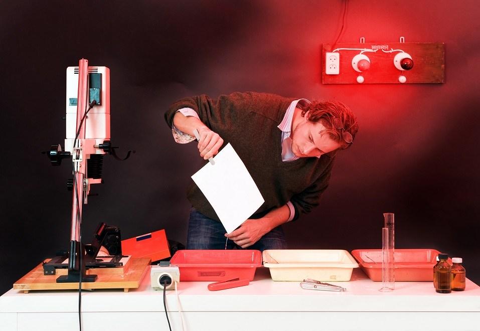 Photographer at work in a darkroom