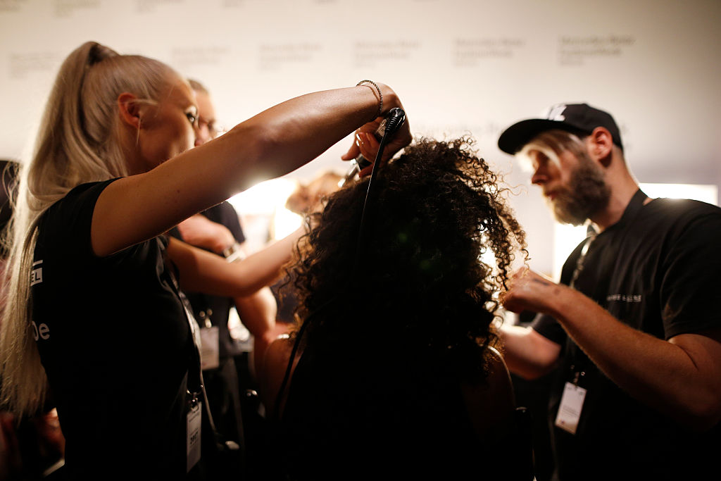 A model is getting her hair done backstage ahead of the Dimitri show during the Mercedes-Benz Fashion Week