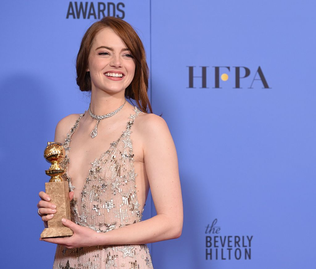 """Emma Stone poses with her award for best actress in a musical or comedy for her role in """"La La Land"""" in the press room"""