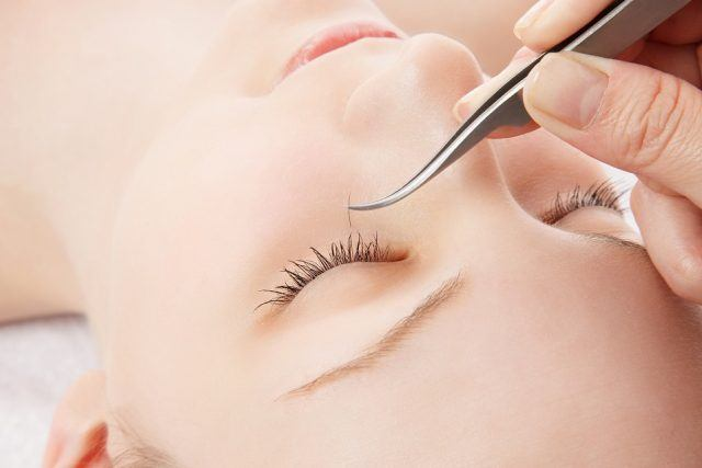 young woman getting eyelash extensions