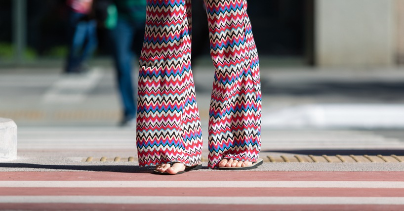 girl crossing the street with rubber sandals and flare pants