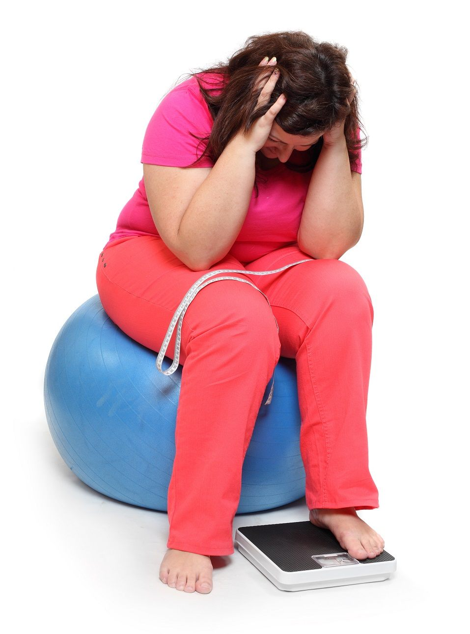 Overweight woman sitting on exercise ball with scale