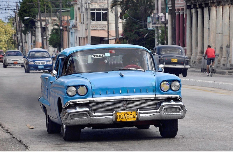 A private taxi (Oldsmobile Super 88, circa 1958) drives along a street on
