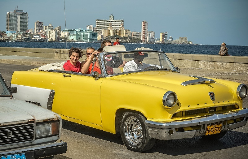 Tourist take a ride in a fully restored Mercury along the coast in Havana on March 18, 2013. Luxury is slowly reappearing in Cuban society after half a century of egalitarianism and austerity, brought upon by the economic reforms of Cuban President Raul Castro.