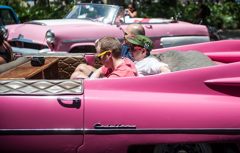 Tourists from the United States sit on an old car in Havana, on April 6, 2015. With sanctions easing, Cuba is bracing for what could be a surge in visitors that could overwhelm its small tourism industry. Americans are starting to discover Cuba, though from them, travel to the island remains limited for now to persons with Cuban relatives or those visiting in a handful of categories such as for academic, sport, religious or cultural purposes. Washington and Havana have been moving toward normalizing relations after more than 50 years of US economic sanctions and are in talks on reopening embassies.
