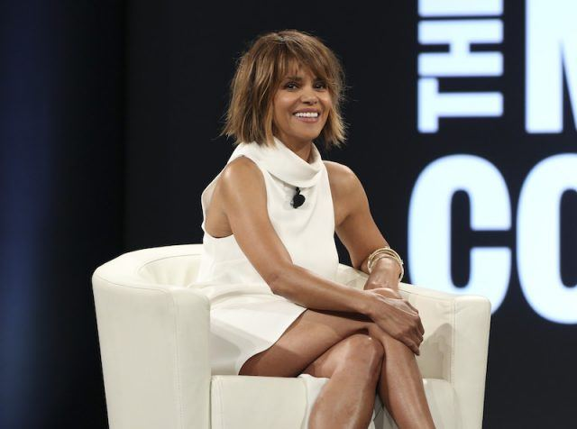 Halle Berry smiling while sitting on a white chair on stage.